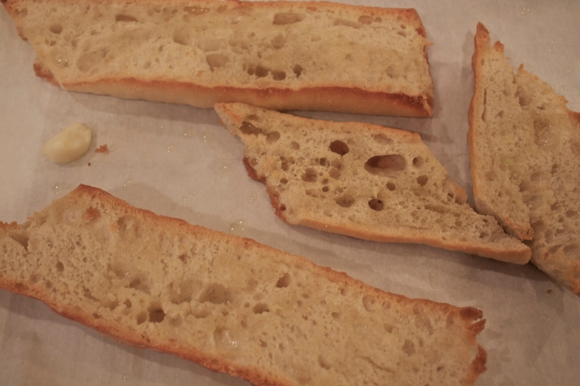 Cut baguette in half, then into diagonal sections, and sprinkle olive oil on top. Into a 400 degree oven for 10 minutes.