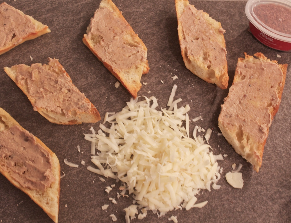 After you have rubbed the crostini with garlic clove, spread each piece with pate.